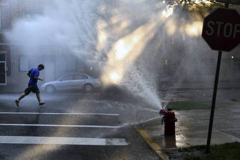 A man runs through an open fire hydrant at the corner of Le Moyne and Leavitt Streets in Chicago.