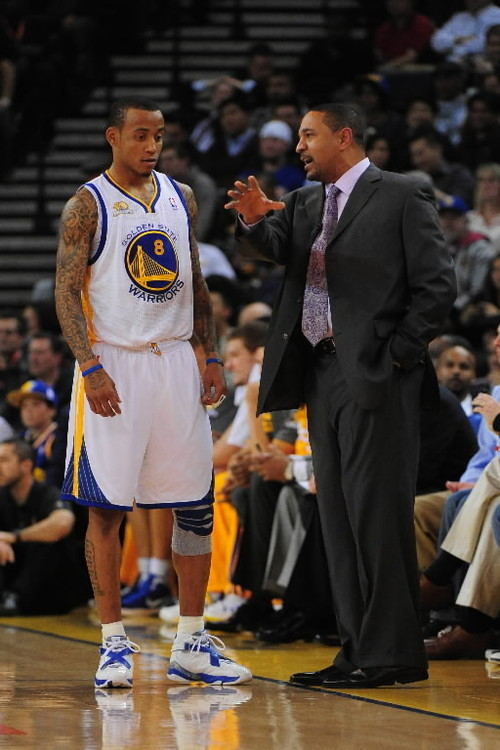 Golden State Warriors head coach Mark Jackson (right) instructs shooting guard Monta Ellis.