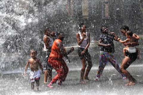 Chicago West Side residents near Augusta Avenue find a way to stay cool on a blistering hot day by playing in water from a fire hydrant.