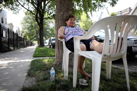 Chicago resident Maria de Jesus Avila, 70, sits in the shade in front of her near West Side home, trying to beat the heat.