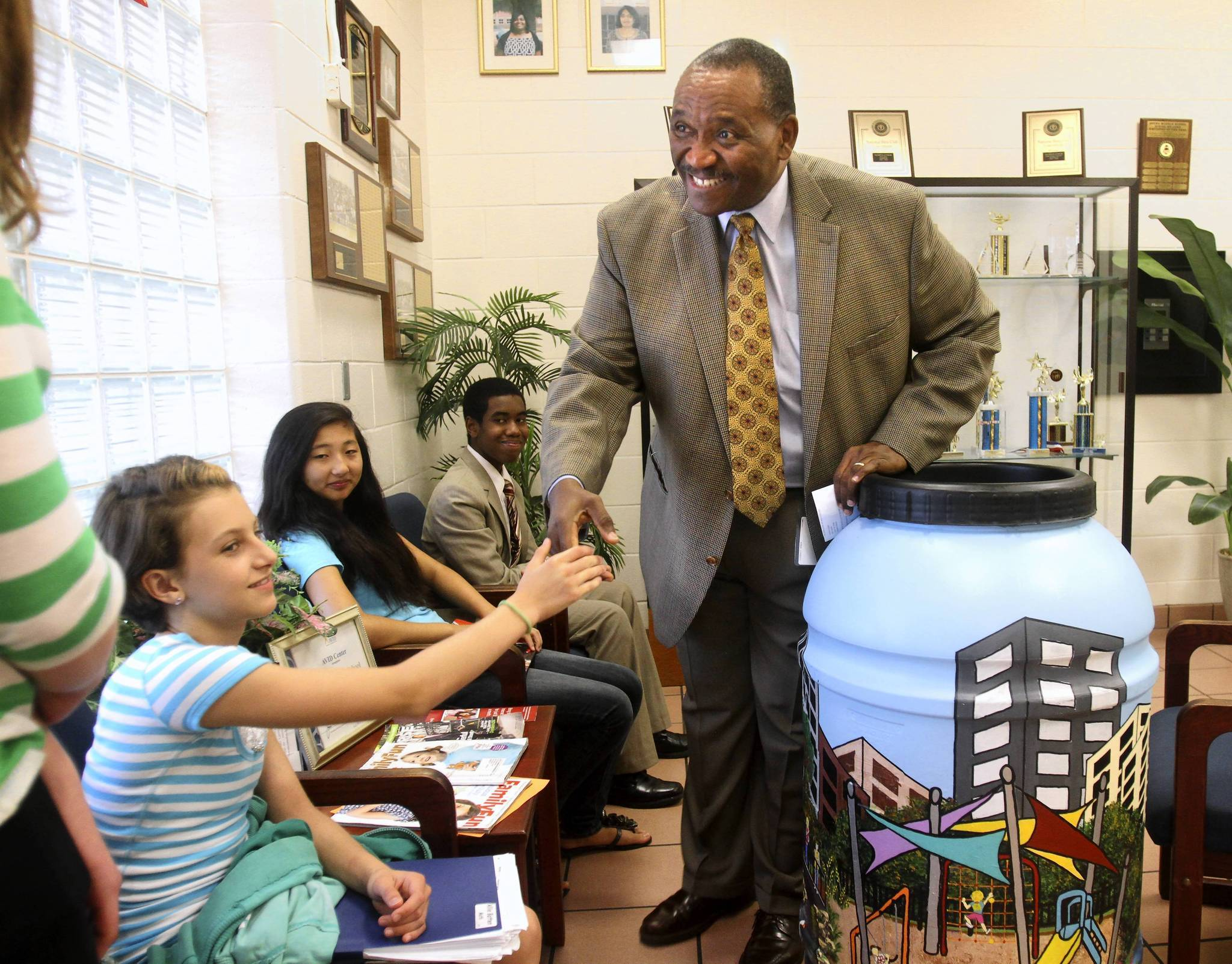 Orange County schools Superintendent Ron Blocker talks to Gotha Middle School students about a rain barrel art project they presented to him, in Gotha, Thursday, June 7, 2012. It was Blocker&#039;s last day as superintendent after 12 years on the job. Students are, from left, Danielle Ibrahim, Allie Batten, Chloe Cal and Nathaniel Calixte.