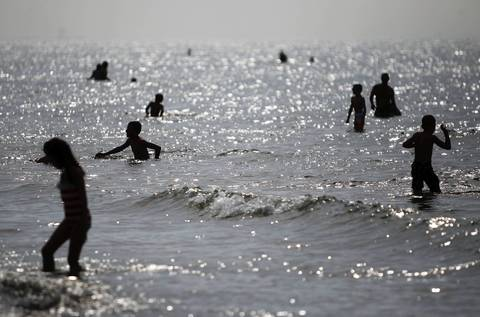 Beach goers cool off in Lake Michigan at the Indiana Dunes State Park in Chesterton, Ind.,. The park, which is adjacent to Indiana Dunes National Lakeshore, is located less than two miles from the Dunes South Shore Line train station.