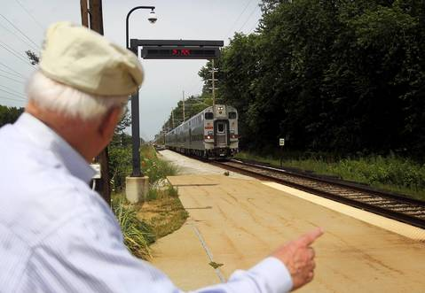 """Kilian Knittel signals to the South Shore Line train at the station in Beverly Shores, Ind.. """"I think this is the niftiest station on the whole line,"""" said Knittel before boarding the train to Chicago."""