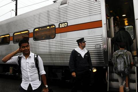 Passengers embark on and disembark from a westbound South Shore Line train at the 11th Street station in Michigan City.