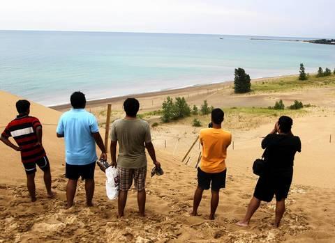 Visitors gaze at Lake Michigan after walking to the summit of Mt. Baldy.