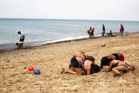 Jessica Rich, 11, clockwise from bottom left, Kaylee Larson, 12, Priscilla Chavez, 12, and Jennifer Rich, 8, dig tunnels at the Indiana Dunes National Lakeshore along Lake Michigan in Beverly Shores. The beach is only a short bike ride from the Beverly Shores South Shore Line train station.