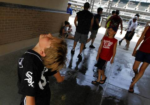 Joseph Lash cools off in a misting spray behind the bleachers before the White Sox-Rangers game.