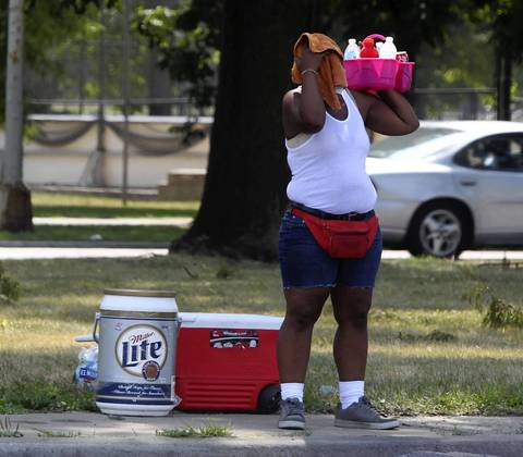 A refreshment vendor can hardly take the heat as she sells her wares on Western Avenue near Archer Avenue in Chicago.