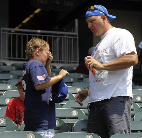 Mike Fischl sprays sunscreen on his son Michael before the game between the Chicago White Sox and the Texas Rangers.