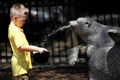 Tyler Stevens, 5, visiting from Indiana, fills his cap at the fountain of spitting bears in Wicker Park.