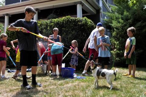 "Family dog ""Jack"" enjoys water fights in front of his owners house in Downers Grove."