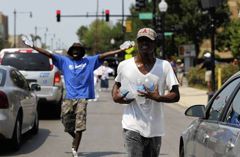 Bryan Pickett, front, and other members of St. Sabina Community Church give out free water at the corner of Racine and 79th Street on Friday.