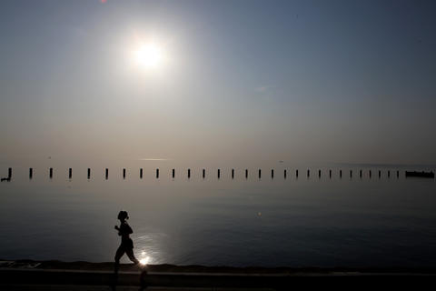The sun is already white hot just after 7 a.m. on Friday morning at Fullerton Avenue beach where joggers sweat it out in the blisteringly hot weather.