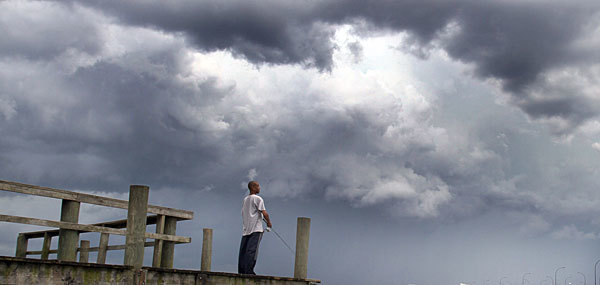 Afternoon storms build Monday evening, July 9, 2012, as a fisherman tries his luck at Lake Underhill.