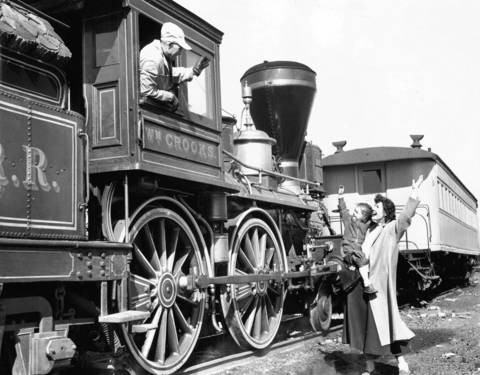 Mrs. Walter A. Edwards and her three-year-old daughter De Witt waves goodbye to the WM Crooks engine at the Railroad Fair in 1948. Marshall Tozer is the mechanic in charge in the cab of the engine.