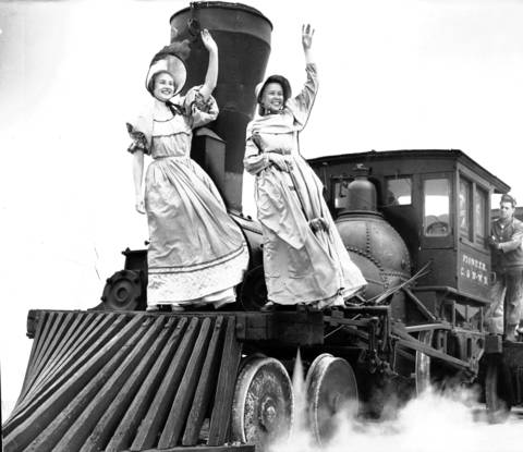 Norma Danielson, left, and Herta Reilly, in pre-Civil War costumes, get a ride on Pioneer, a century old locomotive, as it rolls under its own power during preview of Chicago Railroad Fair, July 15, 1948.
