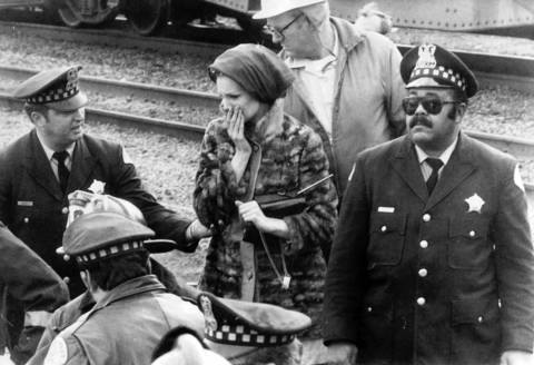 Five hours after the Illinois Central Railroad crash the final three victims are removed from the wreckage to helicopters and ambulances. An unidentified woman reflects as she watches the process, October 30, 1972.