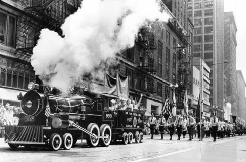 New York Central railroad float, a locomotive on rubber tires owned by American Legion post at Cleveland, O. pours smoke from its stack as it drives along State Street in the parade for the Railroad Fair, June 25, 1949.