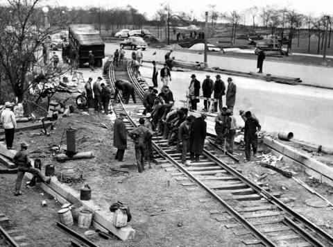 Illinois Central railroad section workers completing the task of laying tracks across Lake Shore. Drive at 28th Street after rush hour traffic had passed. Track will be used to move exhibits into Burnham Park for Chicago Railroad Fair, April 23, 1948.