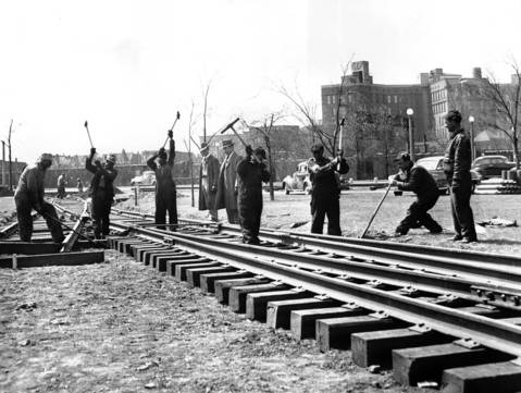 Illinois Central railroad section workers completing the task of laying tracks across Lake Shore. Drive at 28th Street after rush hour traffic had passed, April 23, 1948. Track will be used to move exhibits into Burnham park for the Chicago Railroad Fair.