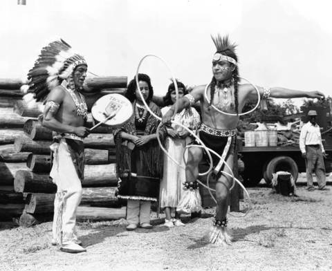 Clememente Whitecloud, drummer, of Jemez Pueblo, New Mexico, Tony Whitecloud, dancing a HoopDance vehicle Iola Quivehema of Second Mesa, Ariz. and Peggy Taptuka of Fort Wingate, New Mexico watch. They were part of the Sante Fe exhibit for the Chicago Railroad Fair, July 18, 1948