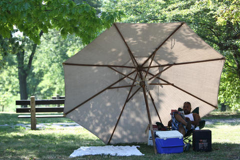 Albert Harris, a contractor who took the day off due to the excessive heat, relaxes in Douglas Park early Tuesday morning. Harris, who brought a propane slow cooker, is making a turkey pot roast while he reads.
