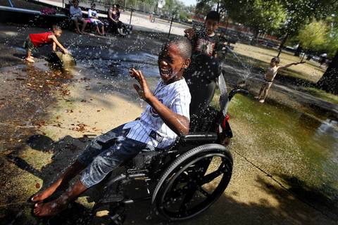 Martrell Stevens, 8, and his wheelchair softball teammates cool off after practice at California Park on Tuesday, a day of near-record heat across Chicago.