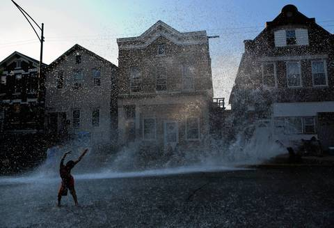 A child cools off in an open hydrant near 19th and Shelby streets in the Pilsen neighborhood of Chicago.