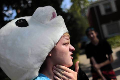 Charlie Conner, 15, of Wilmette, removes his panda suit head for a breather during hot weather. He was skateboarding while wearing the costume while his friend Andrew Stewart, 15, right, was videotaping it for fun. They were on their way to stop in at a nearby Panda Express restaurant to see what reactions they might get.