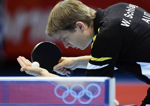 Austria's Werner Schlager serves to China's Wang Hao in the table tennis men's singles round match at the Excel centre in London.