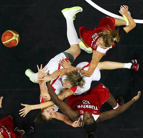 Czech Republic's Ilona Burgrova and Jana Vesela fight for the ball with Turkey's Kuanitra Holingsvorth and Bahar Caglar during the women's preliminary round Group A basketball match.