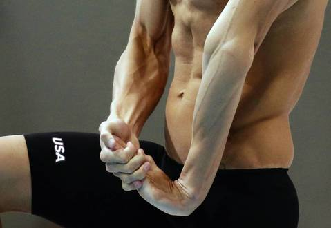 Michael Phelps of the U.S. stretches before his men's 200m butterfly heat at the London 2012 Olympic Games at the Aquatics Centre.