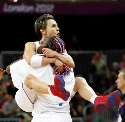 France's Dumerc jumps into the arms of teammate Yacoubou as they celebrate victory against Australia after their women's preliminary round Group B basketball match during the London 2012 Olympic Games.