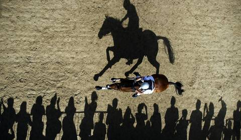 William Coleman of the U.S. rides Twizzel past spectators as he competes in the Cross Country phase of the Eventing competition of the 2012 London Olympics at the Equestrian venue in Greenwich Park.