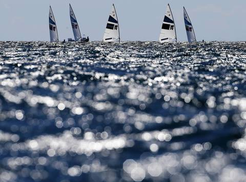 A fleet of Laser class dinghies sails during the second race at the London 2012 Olympic Games in Weymouth and Portland, southern England.