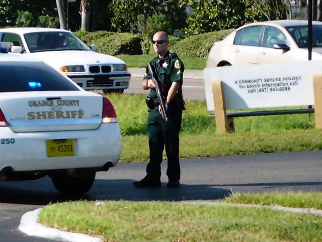 An Orange County deputy sheriff stands armed and ready Thursday afternoon as deputies and the Secret Service responded to threats by a man who was taken into custody for psychiatric evaluation.