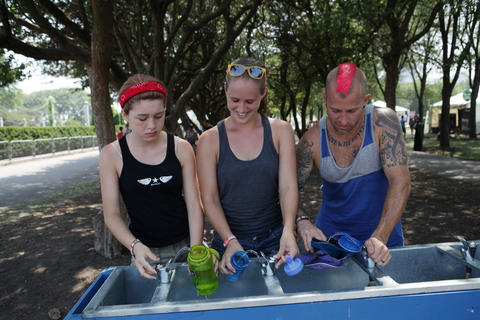 From left, Chole Tokarz, 13, Ellee Tokarz, 18, and Aaron Tokraz, 38, all of Rockford, fill up their water bottles and camelback at Lollapalooza Saturday August 4, 2012.