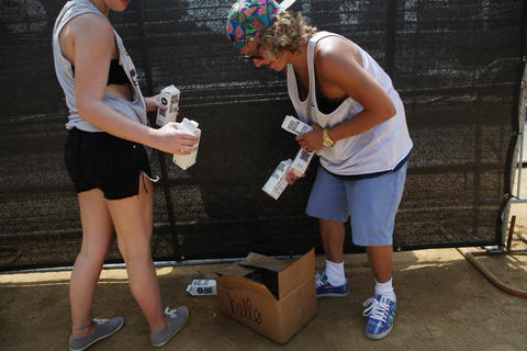 From left, Maggie O'Malley, 17, of Chicago, and her brother Charlie O'Malley, 22, of Chicago grab boxes of water from a box next to the Perry's stage at Lollapalooza Saturday August 4, 2012.