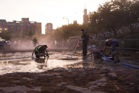 The grounds crew at Lollapalooza works on Grant Park after the severe thunderstorm.