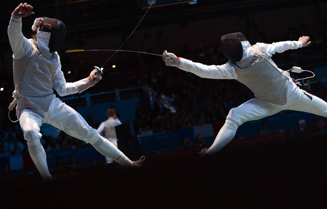 Russia's Renal Ganeev, left, fences against Germany's Sebastian Bachmann during the men's foil team quarterfinals as part of the fencing event of London.