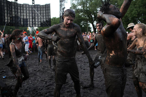 Concert-goers dance in the mud during Calvin Harris's performance at Lollapalooza Saturday August 4, 2012.
