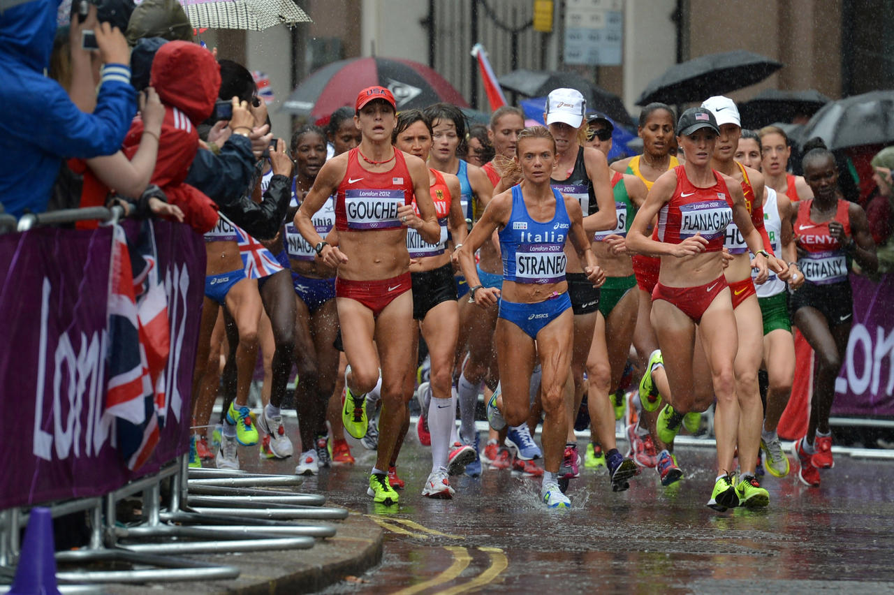 U.S. athletes Shalane Flanagan, right, Kara Goucher, left, and Italy's Valeria Straneo, center, run under heavy rain during the women's marathon at the London 2012 Olympic Games.