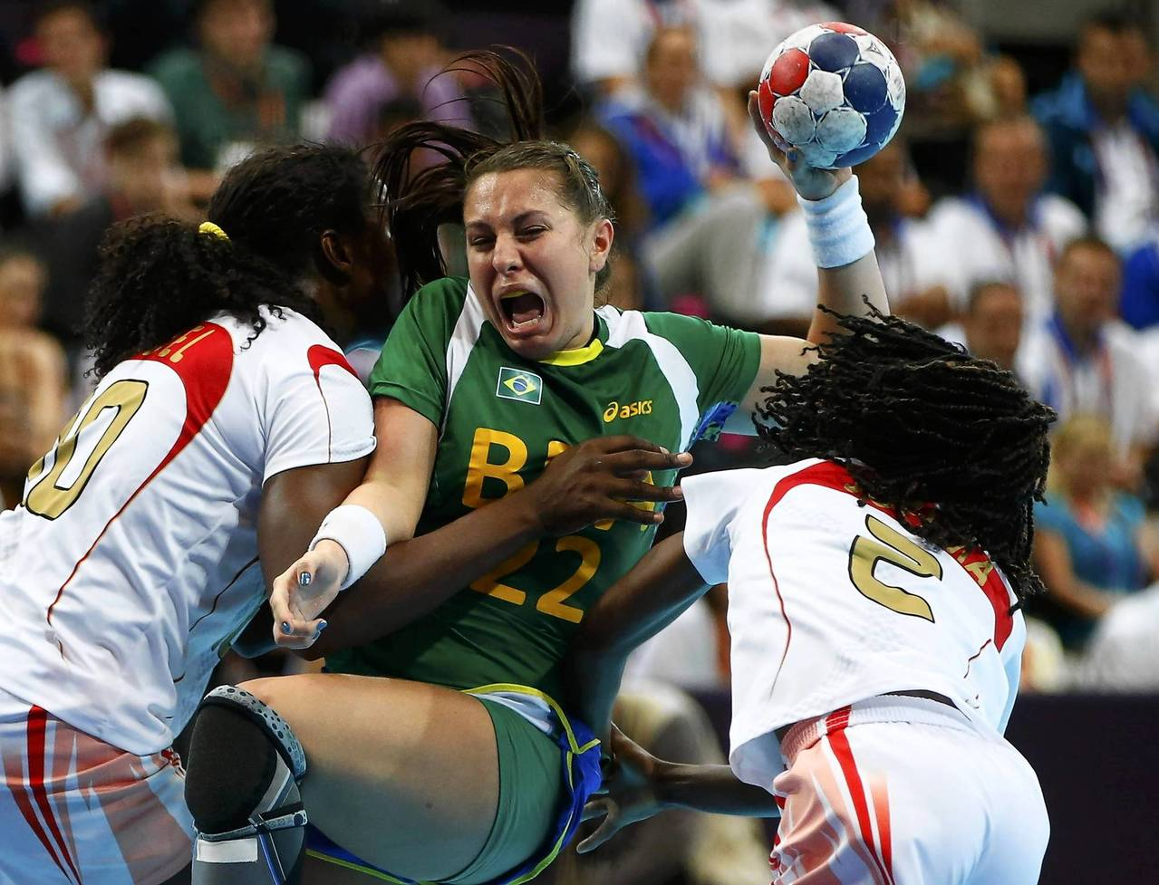 Angola's Isabel Fernandes and Joelma Viegas challenge Brazil's Mayara Moura in their women's handball Preliminaries Group A match at the Copper Box venue.