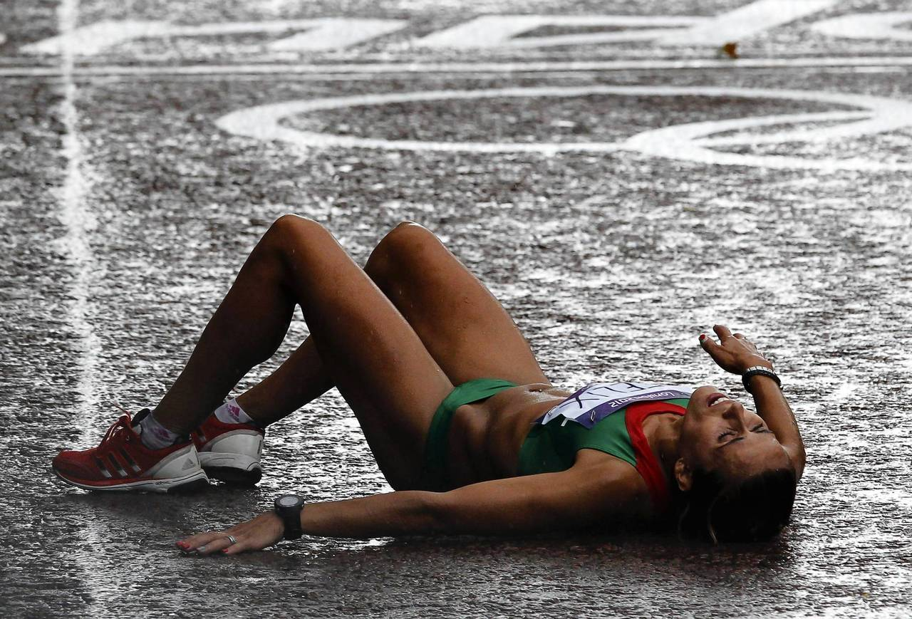 Portugal's Ana Dulce Felix lays on the ground after competing the women's marathon final at the London 2012 Olympic Games.