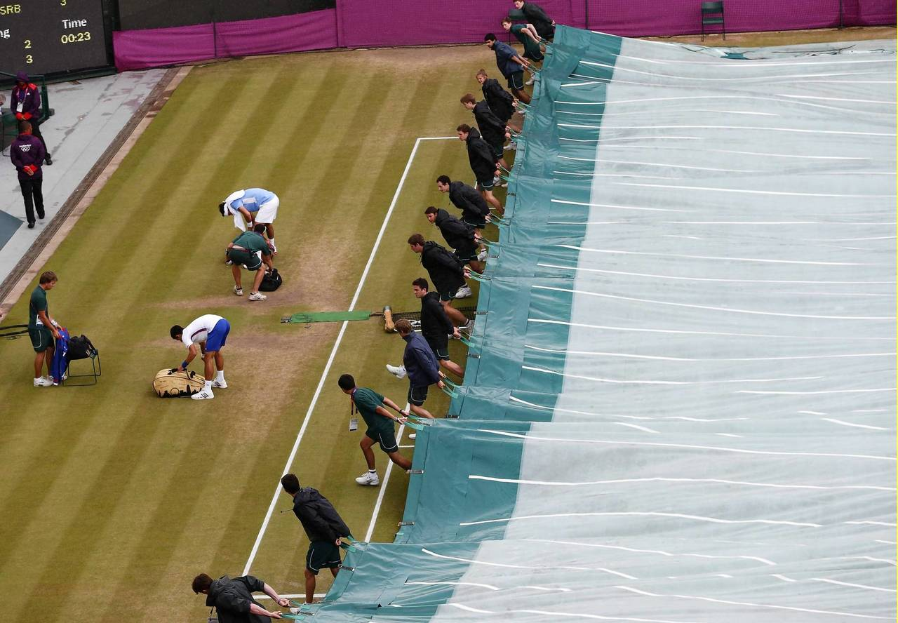 Workers deploy a tarp over the court as rain delays the men's singles tennis bronze medal match between Argentina's Juan Martin del Potro (left, in blue) and Serbia's Novak Djokovic (left, in white) at the All England Lawn Tennis Club during the London 2012 Olympic Games.