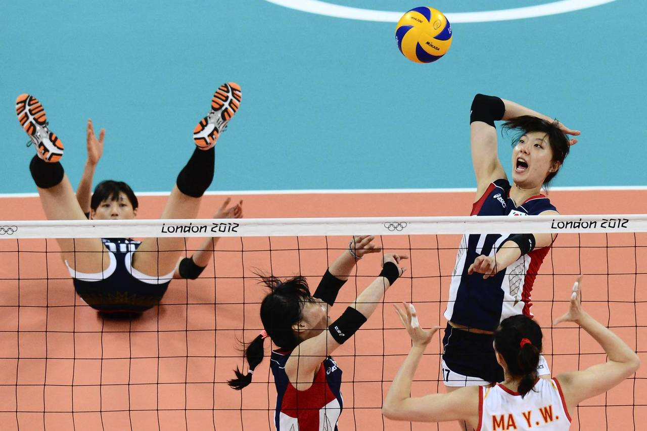 South Korea's Yang Hyo-Jin (right, top) spikes as China's Ma Yunwen (right, bottom) attempts to block during the Women's preliminary pool B volleyball match between China and South Korea in the 2012 London Olympic Games in London.