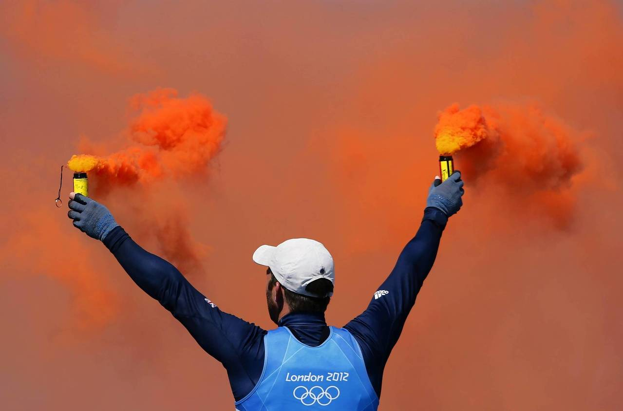 Britain's Ben Ainslie holds flares as he celebrates winning the men's finn class sailing competition.