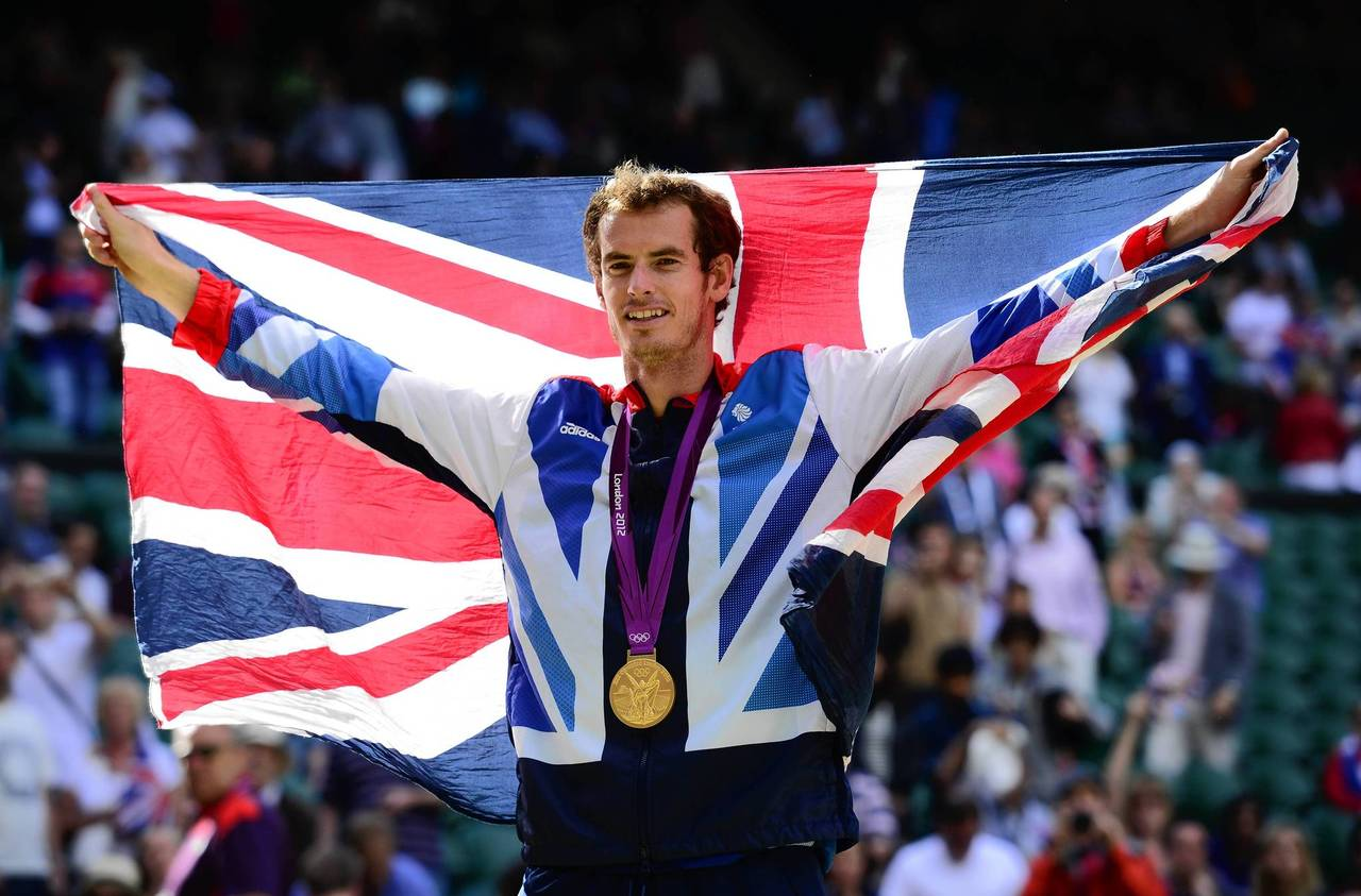 Great Britain's Andy Murray poses with his gold medal and the Union Jack at the end of the men's singles tennis tournament.