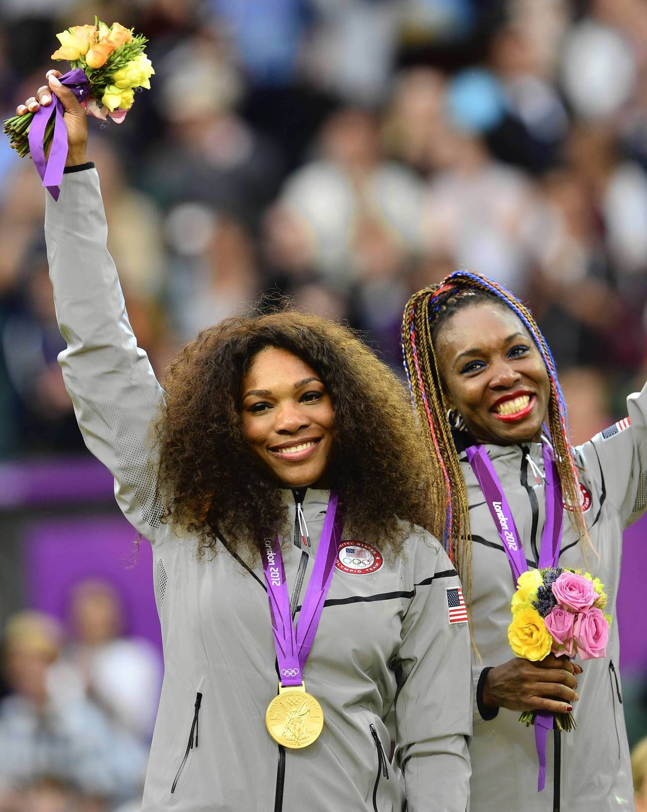Serena and Venus Williams celebrate on the podium after receiving their gold medal for winning the doubles tennis tournament at the All England Tennis Club in Wimbledon.