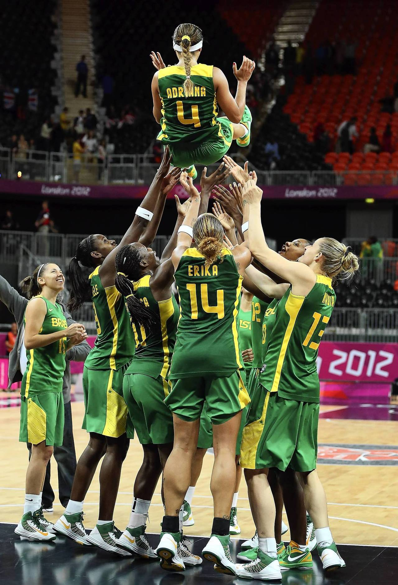Brazil's Adriana Pinto is thrown into the air by teammates to honor her final game with the Brazil National Team following a game against Great Britain.